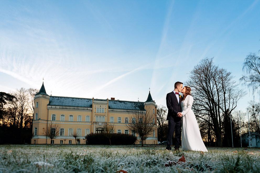 Küssendes Brautpaar vor dem Schloss Kröchkendorff in Brandenburg