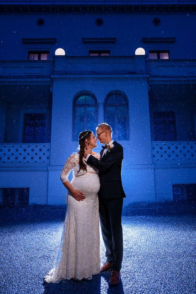 Schwangere Braut und Bräutigam im Regen