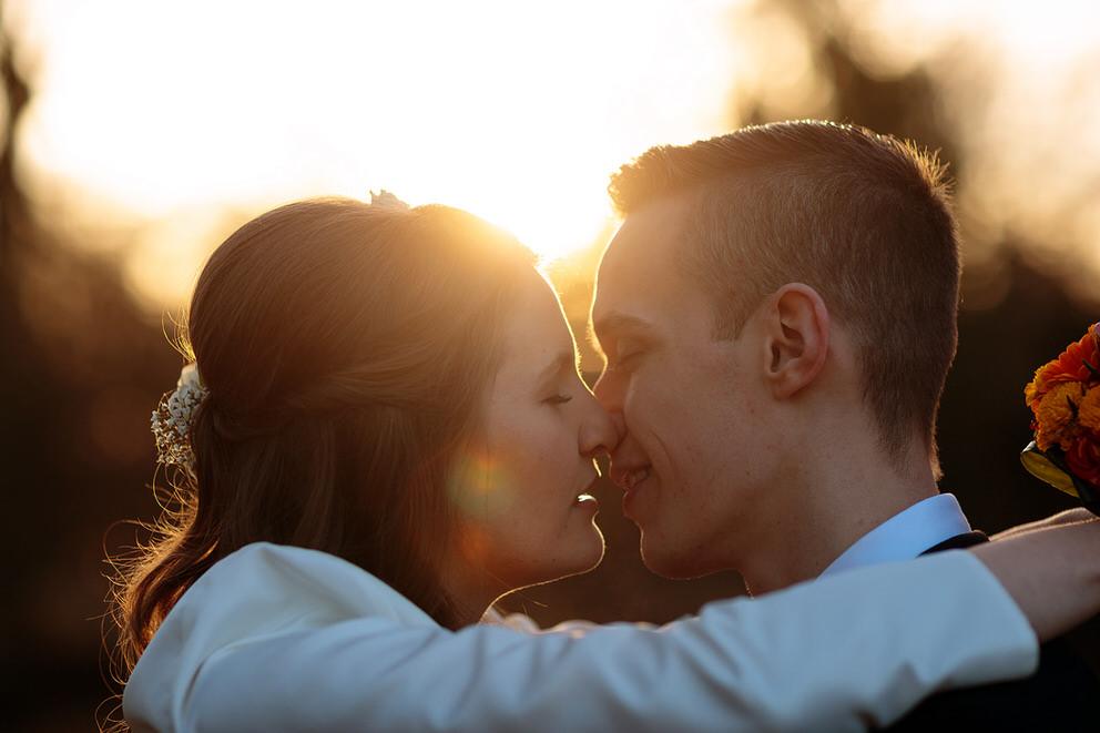 Brautpaar küssend im Sonnenuntergang