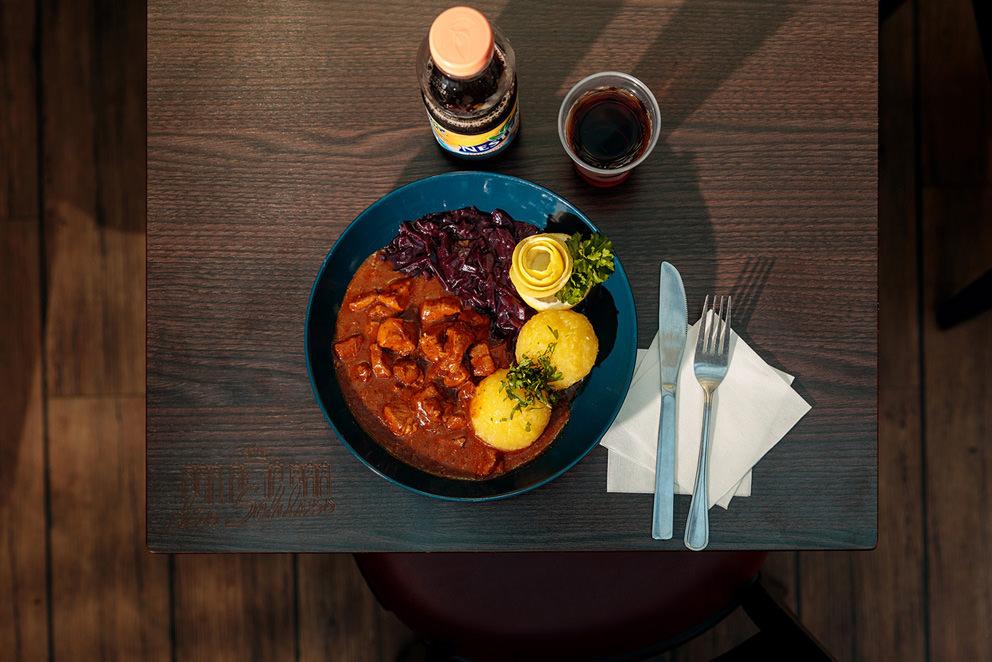Gulasch mit Kloessen und Rotkohl und einem Getraenk zum Mittagessen