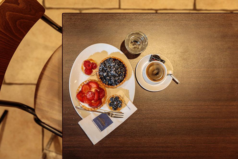 Törtchen und Backwaren mit Espresso und einem Wasser für ansprechende Food-Bilder