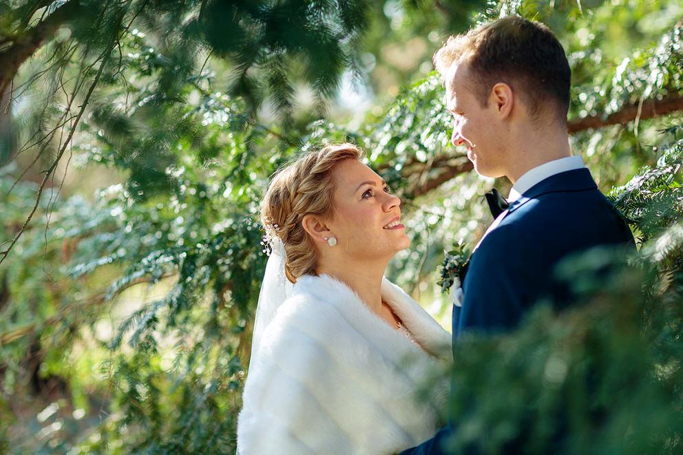 Brautpaar unter Tannen im Park