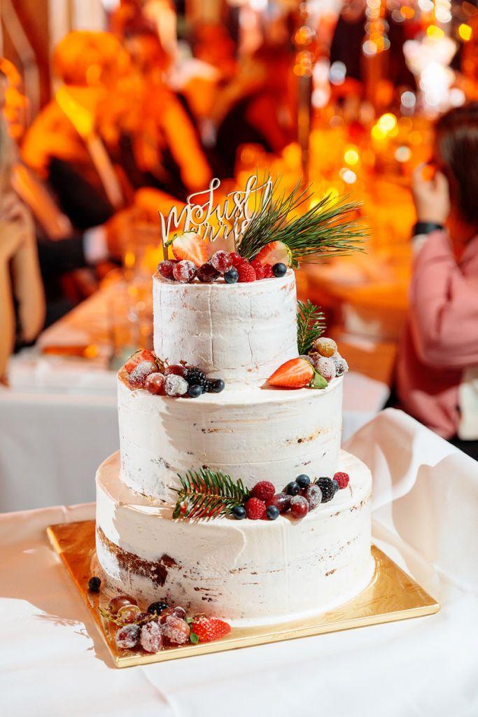 Winterliche Hochzeitstorte mit Zweigen und Beeren