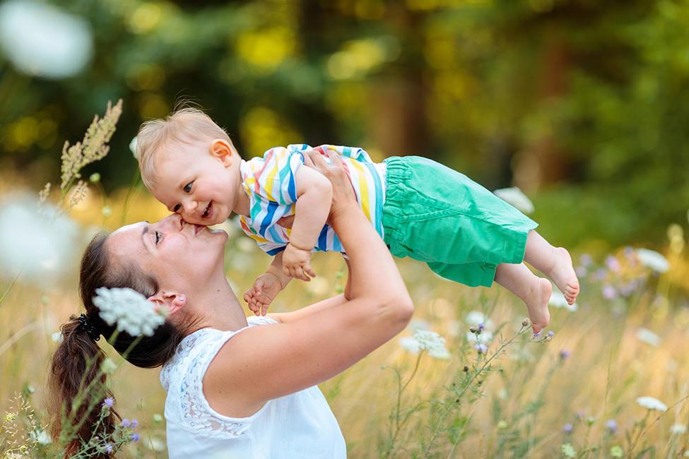 Mama und Kind spielen auf Blumenwiese