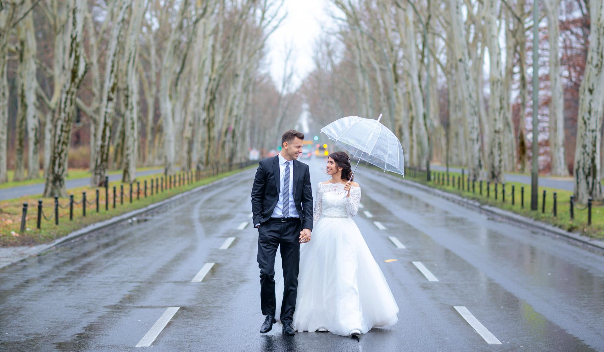 Brautpaar spaziert mit Regenschirm in Berlin