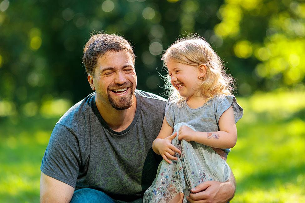 Papa und Tochter lachen herzlich auf Wiese