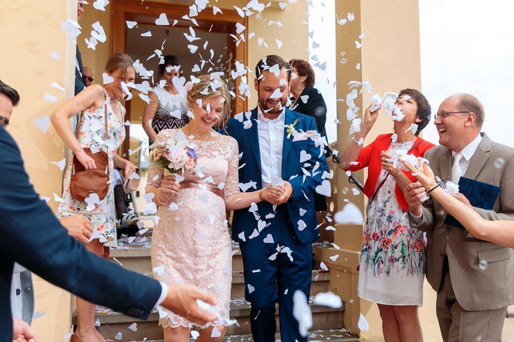 Brautpaar mit Blumenregen nach der Trauung