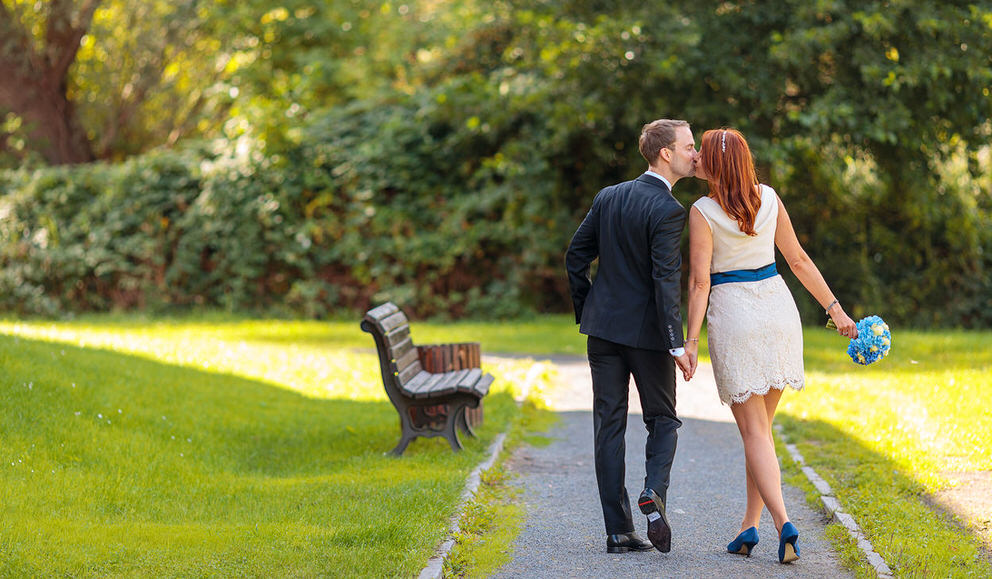 Brautpaar spaziert küssend durch den Park