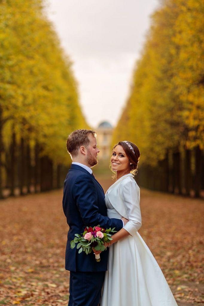 Brautpaar zwischen einer herbstlichen Baum Allee