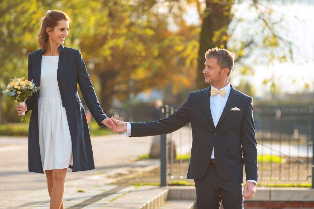 Brautpaar spaziert Händchen haltend am Wasser