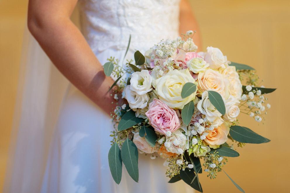 Brautstrauss mit Rosen und Pfingstrosen vor gelber Wand