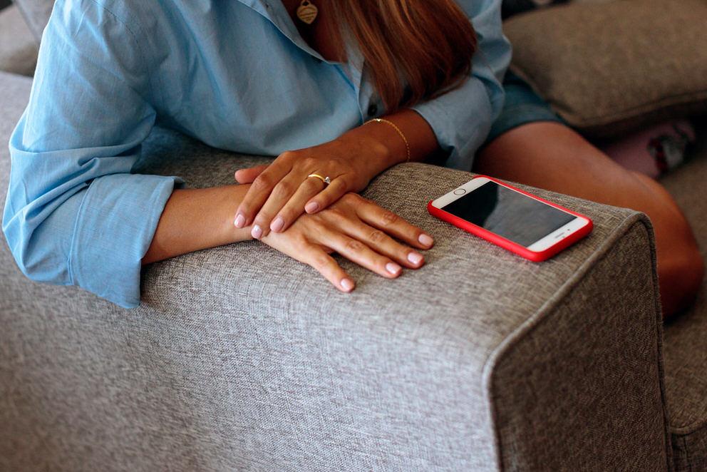 Frau hat Handy neben sich auf dem Sofa liegen