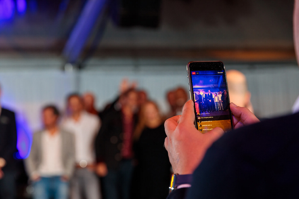 Mann hält Handy in der Hand für Live Aufnahme bei Event