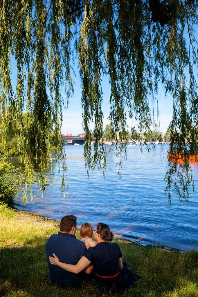 Familie sitzt am Ufer und blickt auf See
