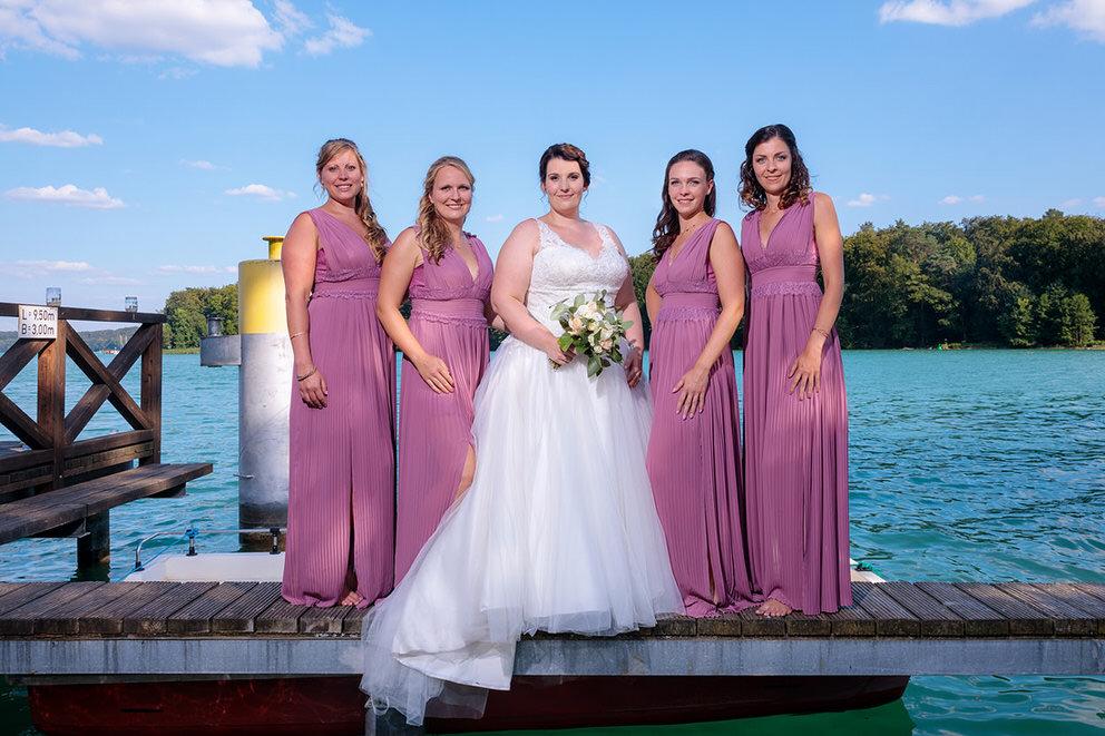 Die Braut macht ein Foto mit ihren Brautjungfern am Wasser