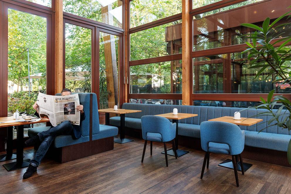 Gast liest in seiner Zeitung in Berliner Restaurant