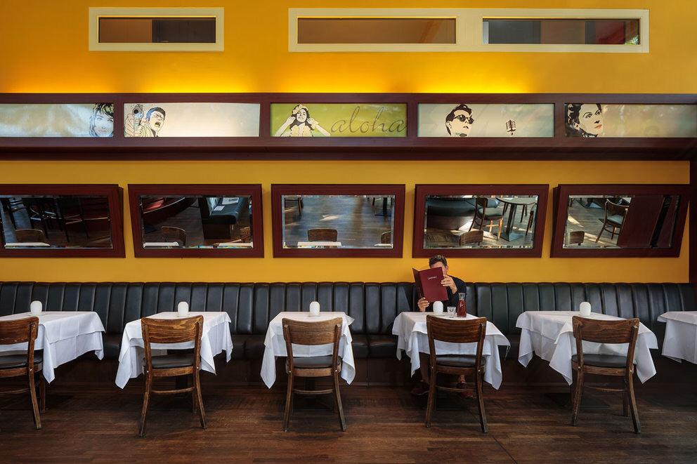 Wandansicht mit Tischen, Stuehlen und Baenken in Berliner Restaurant