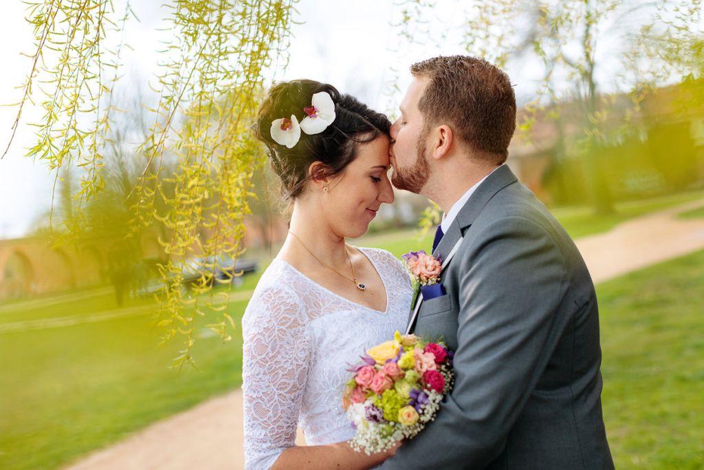 Bräutigam gibt seiner Braut einen Kuss auf die Stirn