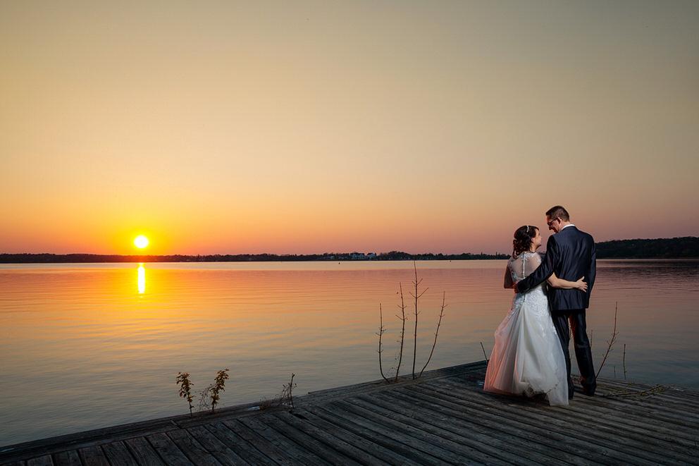 Brautpaar steht am Wasser und blickt dem Sonnenuntergang entgegen