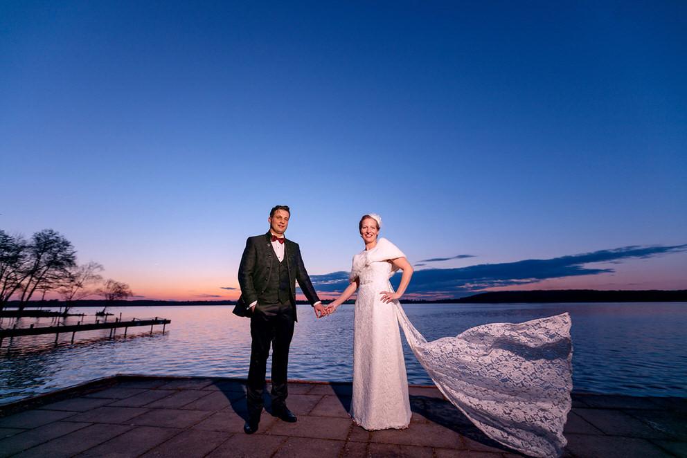 Brautpaar steht am Wasser mit dramatischem Abendhimmel