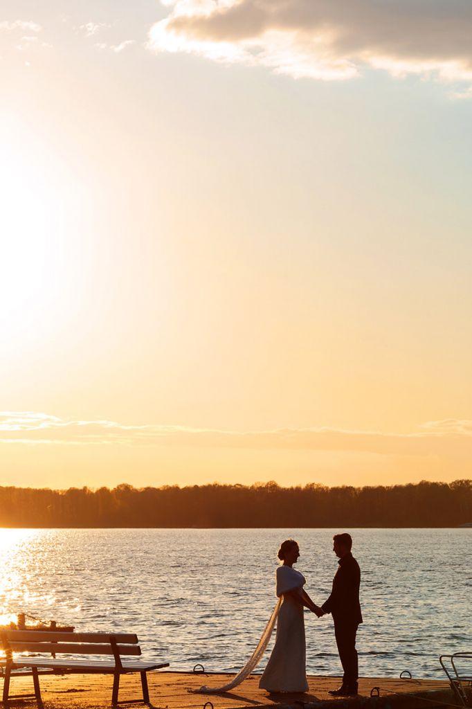 Brautpaar steht Hand in Hand am Wasser