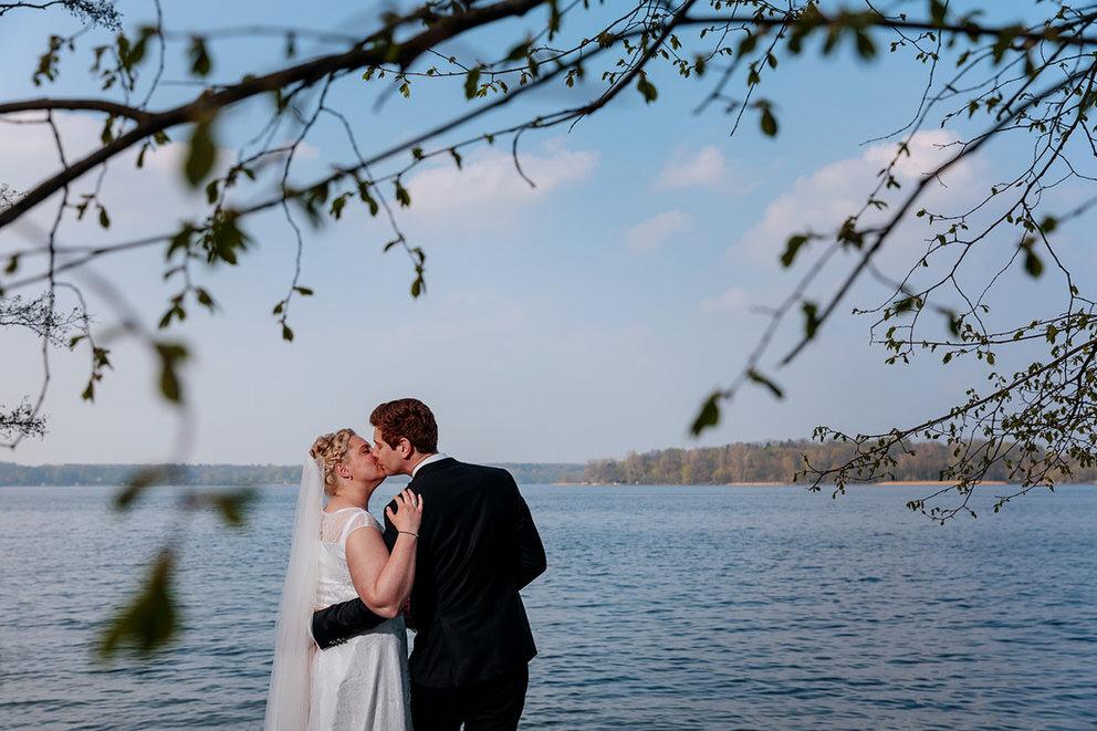 Brautpaar steht am Seeufer und küsst sich