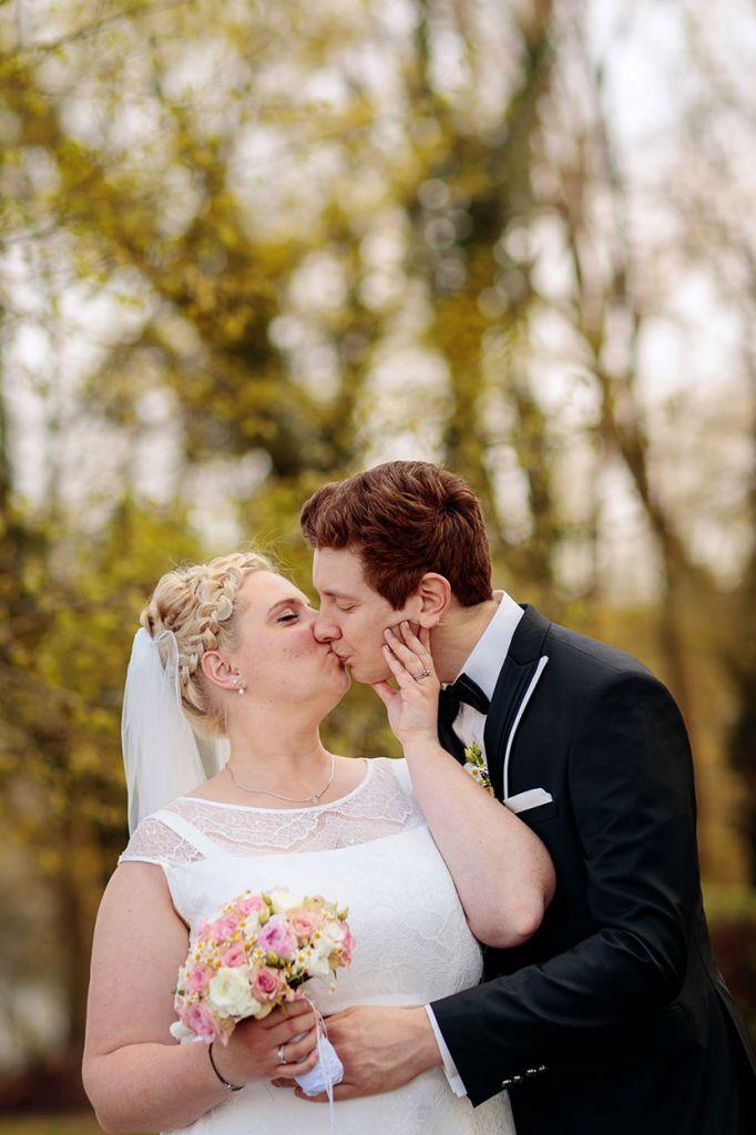 Braut und Bräutigam küssen sich für Paarfotos