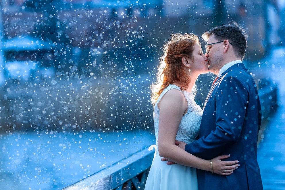 Brautpaar küsst sich bei Regen