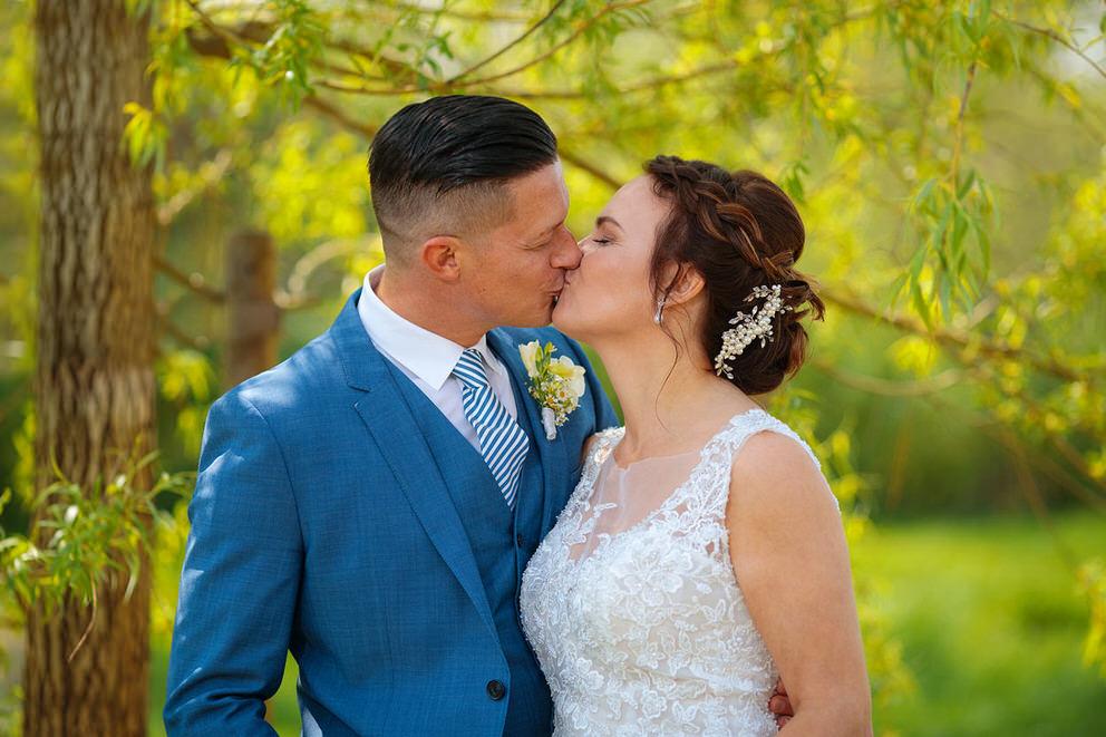 Brautpaar kuesst sich im Garten nach standesamtlicher Trauung