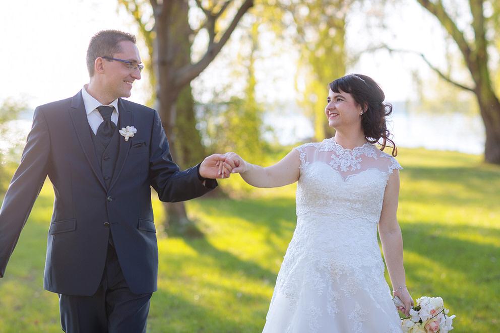 Brautpaar spaziert über Wiese im April