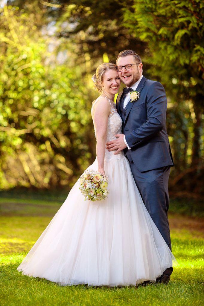 Brautpaar steht im Park