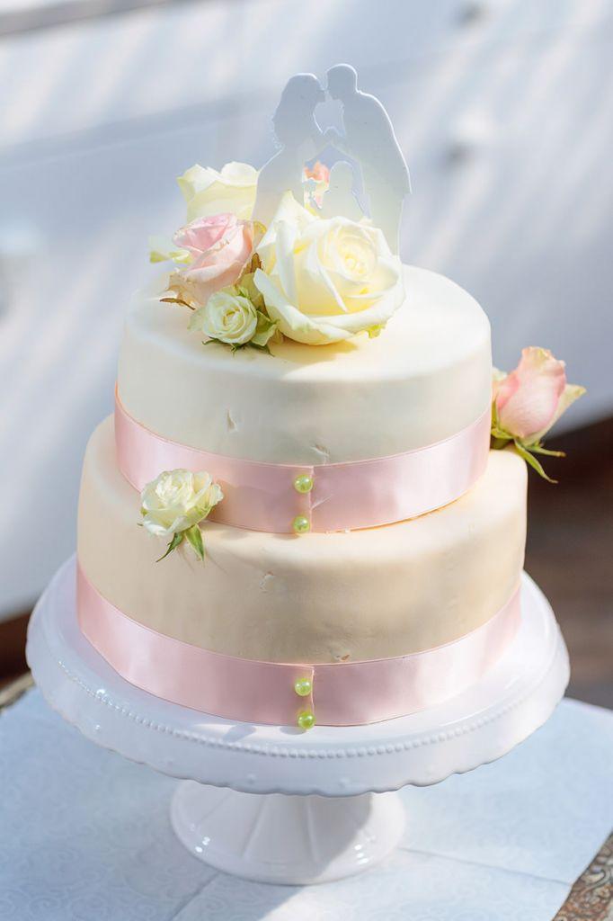 Hochzeitstorte mit Rosen und rosa Band