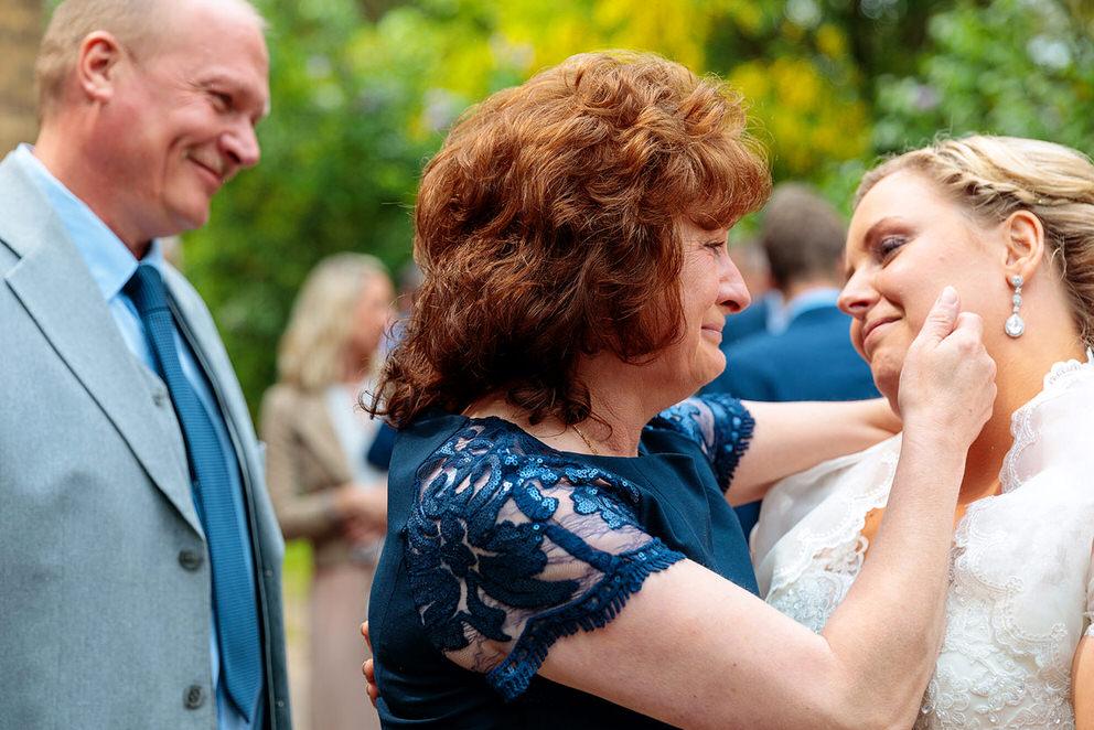Mutter und Braut liegen sich weinend in den Armen