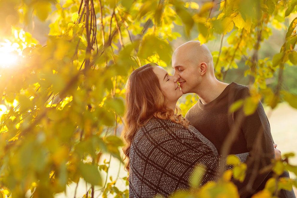 Das verlobte Paar küsst sich unter einem Baum