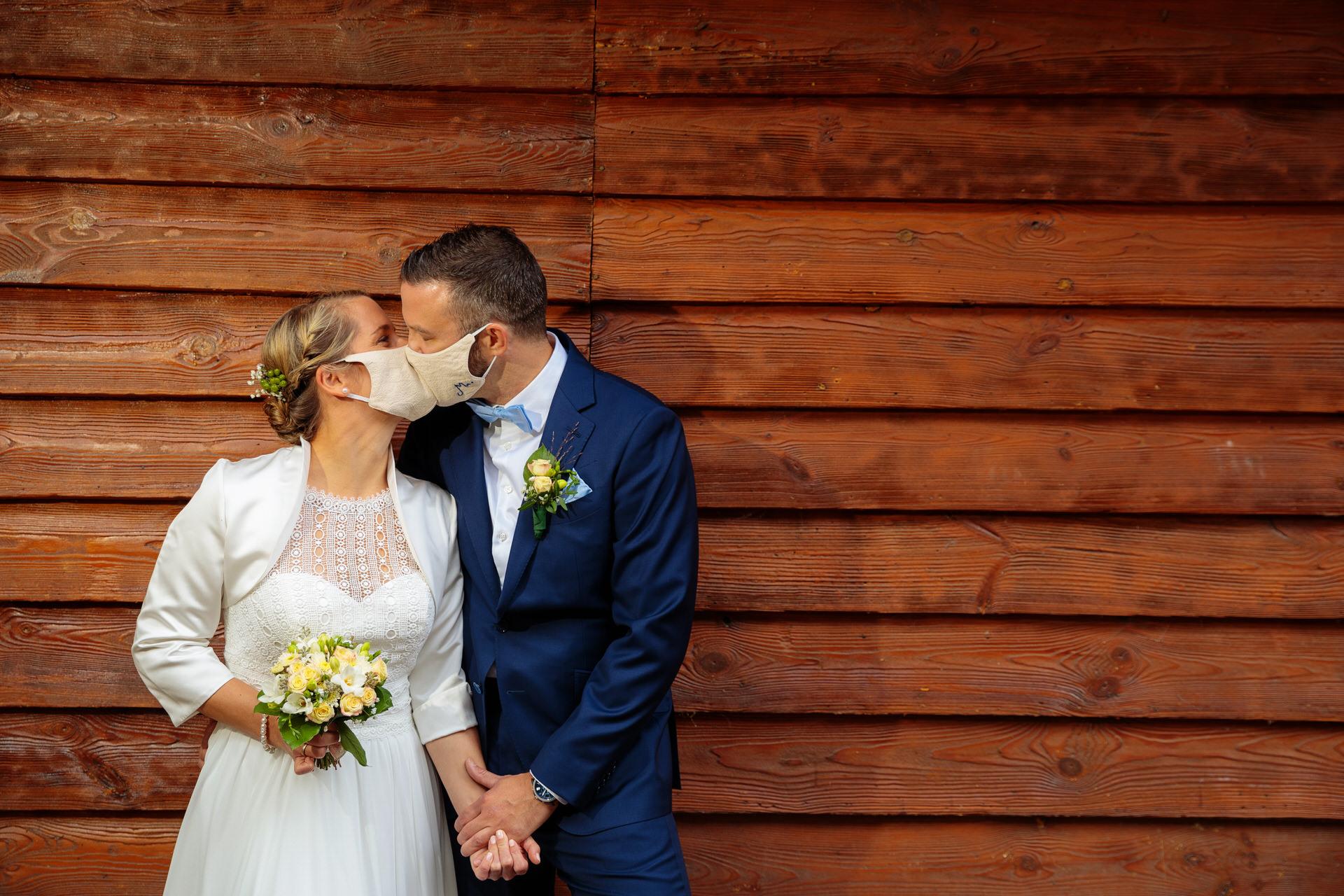 Brautpaar gibt sich mit Maske einen Kuss bei einer Hochzeit im Corona Jahr