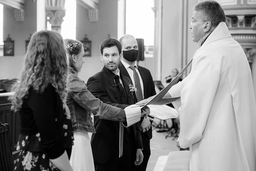 Brautpaar bei kirchlicher Trauung und Trauzeugen mit Maske