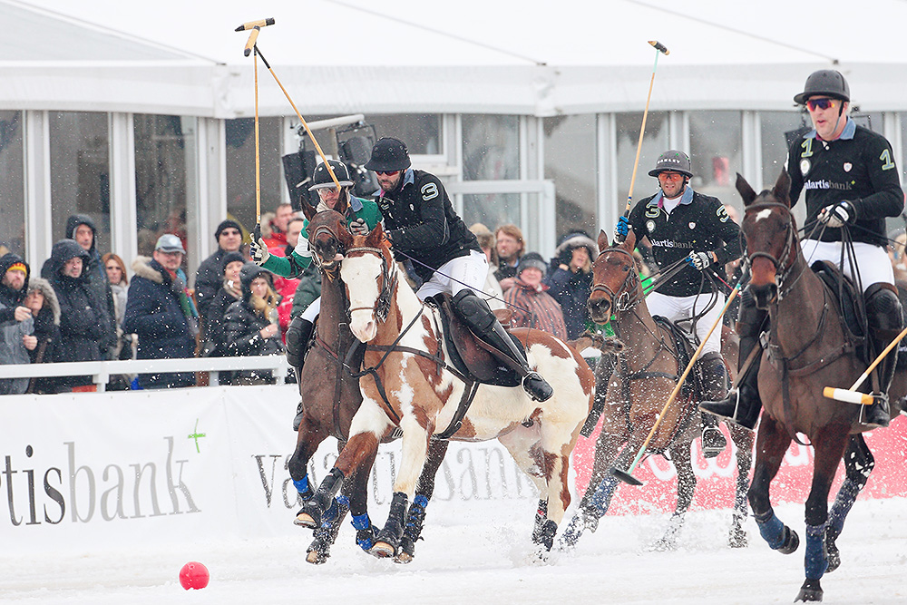 Polo players chasing the red ball during their Snow Polo World Cup match in Kitzbuehel