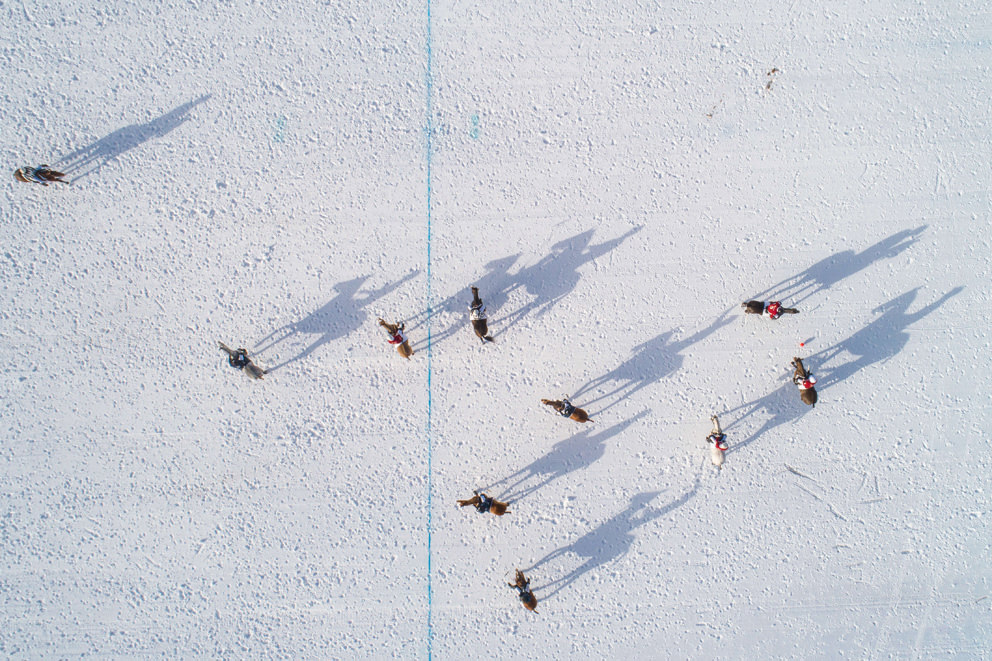 Aerial drone photo of horses and their shadows during a polo tournament in st moritz switzerland