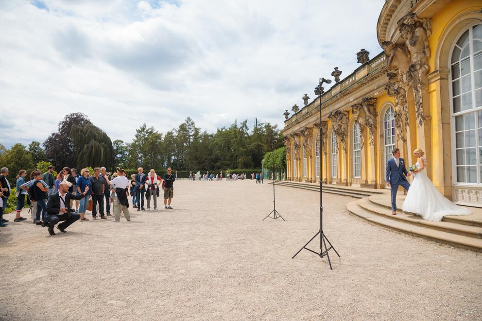 Hochzeitsfotograf in Potsdam fotografiert Brautpaar vor dem Schloss Sanssouci mit Touristen im Hintergrund