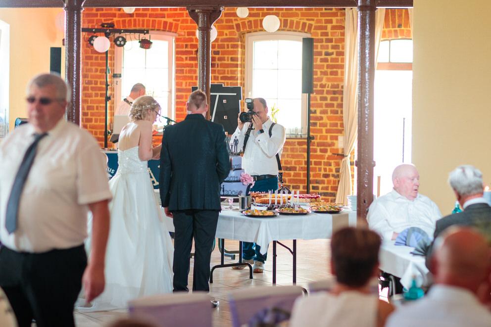 Hochzeitsfotograf in Schlieben fotografiert Brautpaar beim Anschnitt der Hochzeitstorte