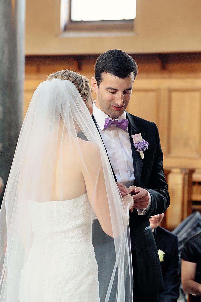 Bräutigam steckt Ring an den Finger seiner Braut