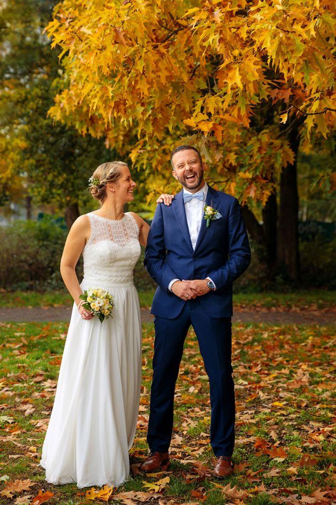 Braut und Bräutigam stehen lachend im herbstlichen Park