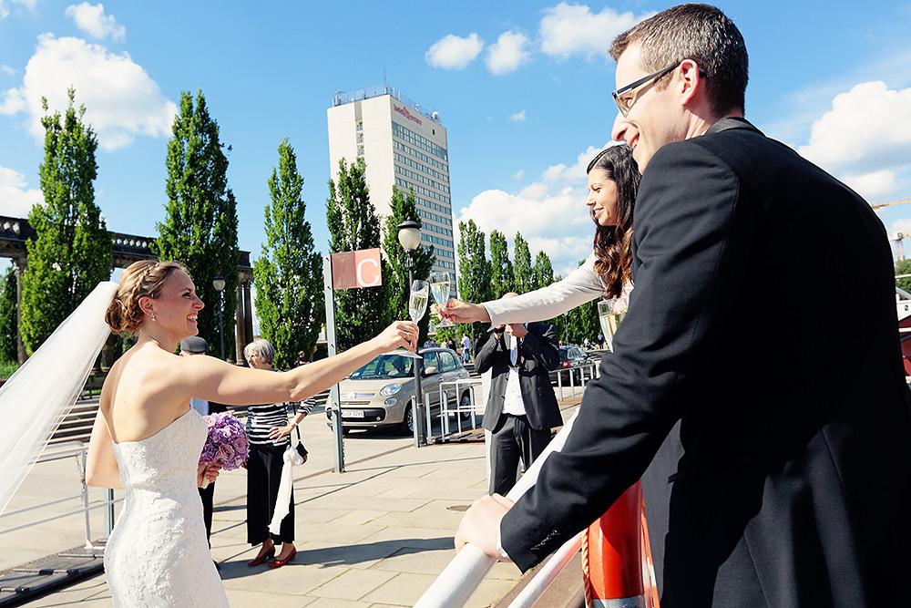 Braut und Hochzeitsgast stoßen mit Sekt an
