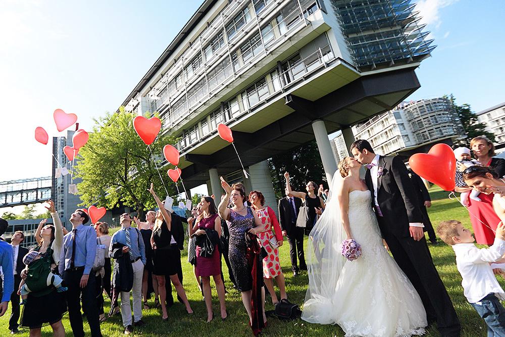 Brautpaar küsst sich während Hochzeitsgäste Ballons steigen lassen