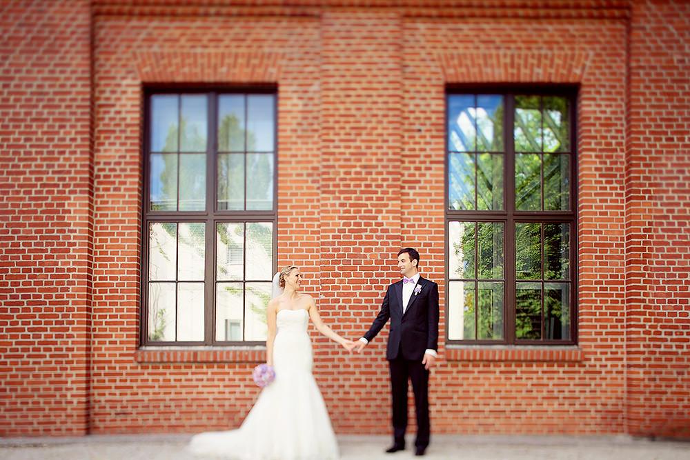 Brautpaar steht vor Backsteinwand