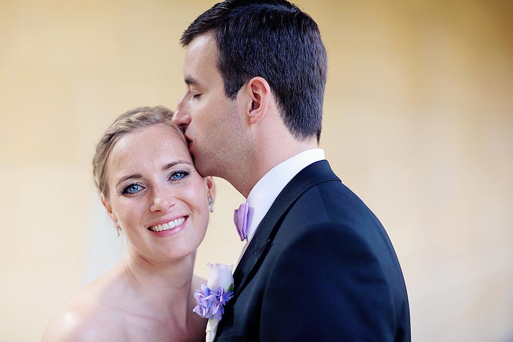 Bräutigam gibt seiner strahlende Braut einen Kuss