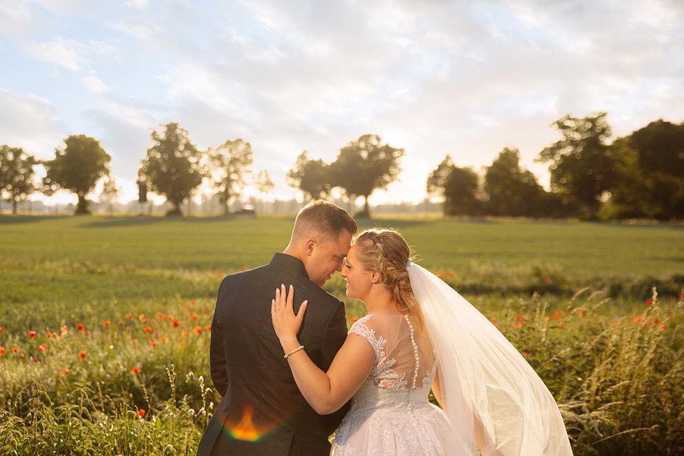 Strahlendes Brautpaar bei Fotos im Mohnblumenfeld bei Sonnenuntergang